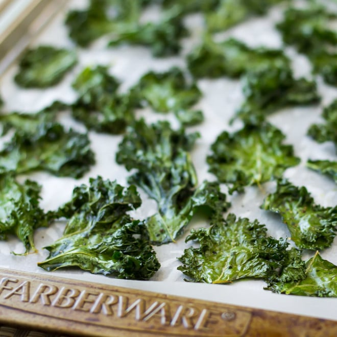 Crispy Kale Chips on a baking sheet lined with parchment paper.