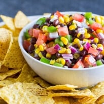Black Bean Salsa in a white bowl surrounded by tortilla chips.