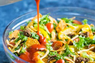 Dorito taco salad in a clear bowl with french dressing being poured onto it.