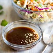 A square photo of a bowl of Asian Salad Dressing sitting in front of a bowl of Chinese Chicken Salad.