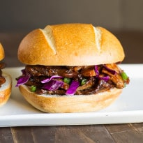 A photo of two buns with delicious 3-day beef brisket , served with red cabbage slaw on a white plate against a dark wood background.