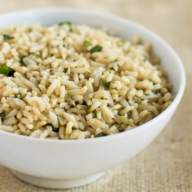 White bowl of Chiptole's Cilantro Lime Rice, pictured against a light brown background.