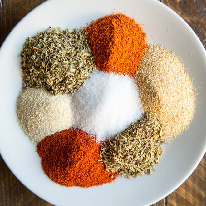 7 piles of spices on a white plate on a dark wooden background.