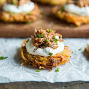 Potato Latkes with Barbecue Pulled Pork! Crispy potato pancakes, shredded pork, and a sour cream and scallion topping. Basically the best appetizer, ever.
