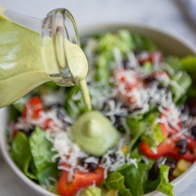 Cilantro Lime Dressing - a photo of a clear jar full of a green cilantro lime dressing being poured onto a salad - click photo for full written recipe