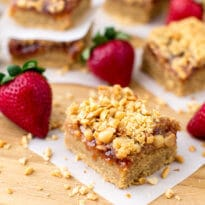 Peanut Butter and Jelly Bars have a peanut butter cookie crust topped with strawberry jam and crunchy peanuts. Kids and adults alike will gobble these up!