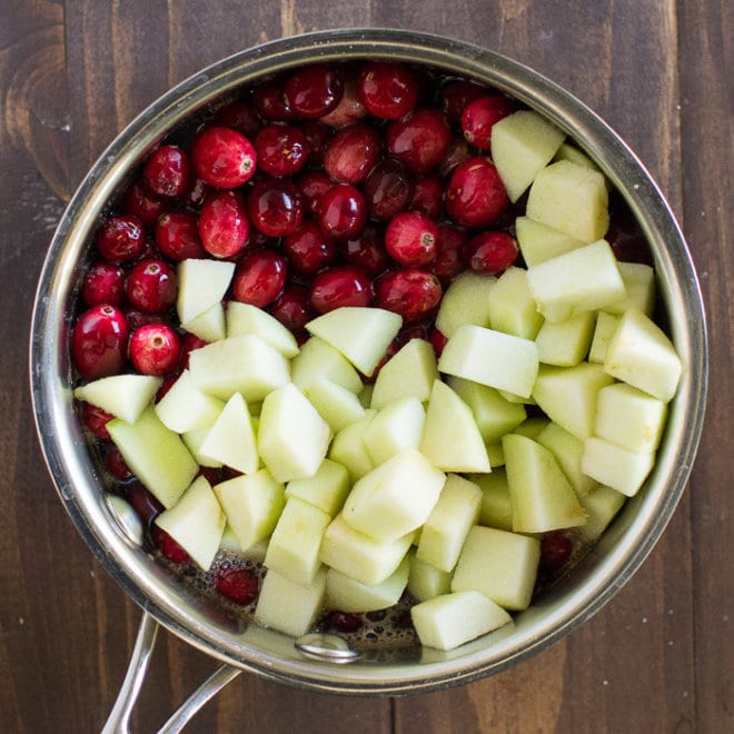 Chunks of apples and cranberries in a silver pot.