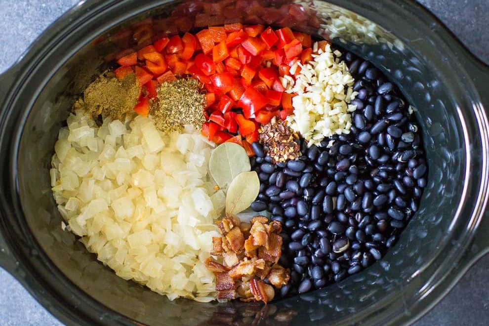 An overhead photo of the inside of the crockpot with all the ingredients, clockwise from the top: white onion, red bell pepper, minced garlic, blackl beans, and bacon.. Topped with the spices: cumin, bay leave, oregano, and red chili flakes.