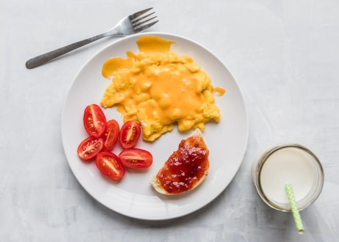 10 Toddler Breakfast Ideas - a photo of a biscuit half with jelly, tomato slices, and scrambled eggs on a white plate with a white background - click photo for full written recipes