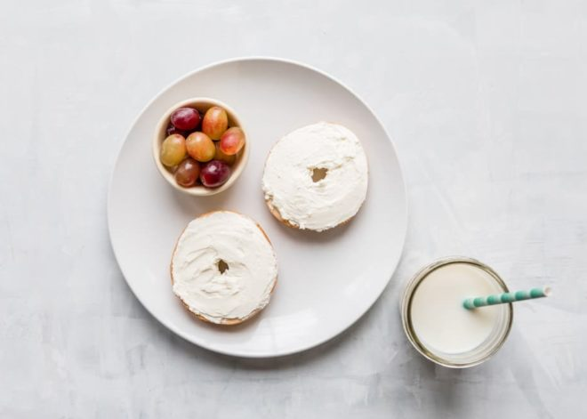 10 Toddler Breakfast Ideas - a photo of two bagels covered with cream cheese next to a cup of grapes on a white plate and white background - click photo for full written recipes