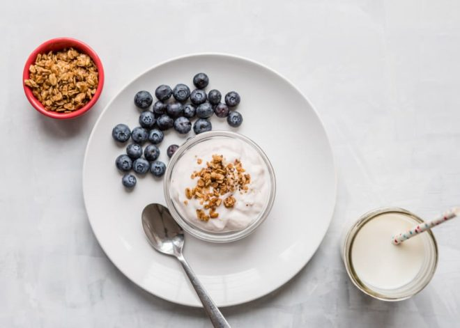 10 Toddler Breakfast Ideas - a photo of a red cup of granola, a white plate with blueberries next to a cup of yogurt topped with granola on a white background - click photo for full written recipes