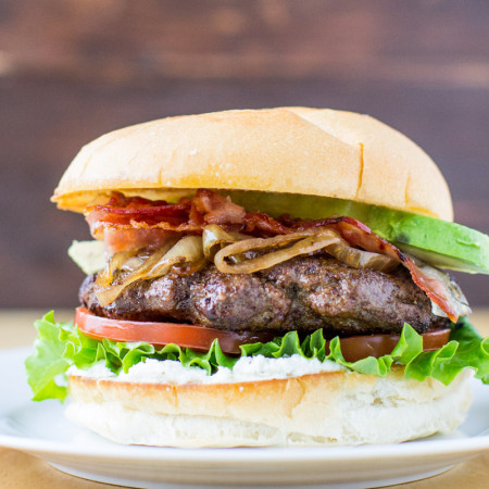 A super juicy burger flavored with red wine and fresh herbs on a soft, grilled roll slathered in Boursin cheese. Top it off with crisp lettuce, fresh tomato slices, caramelized balsamic onions, smoky bacon, and luscious avocado for the ultimate flavor fest!