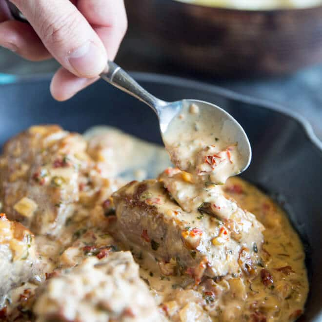 A photo a hand holding a spoon, placing sauce on one of four servings of pork tenderloin in a blue cast iron skillet. The tenderloin is in a sun dreid tomato creak sauce, and visible in the light pink-tinted sauce are small pieces of sun-dried tomatoes.