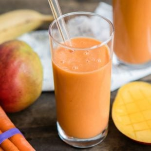 Mango carrot smoothie in a clear glass.