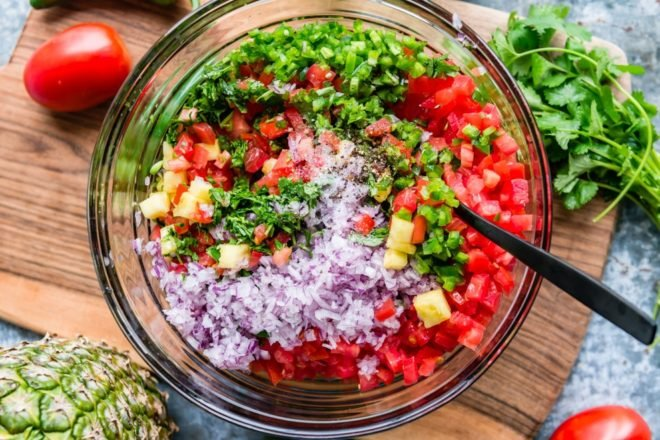 An easy recipe for Pineapple Salsa. Loaded with plenty of fresh pineapple, tomatoes, red onion, jalapeños, and cilantro, this is your answer to spring and summer snacking! It's perfect with chips or on your favorite grilled meat, and it's good for you!