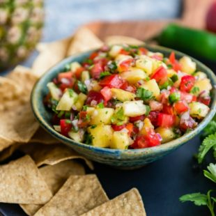 Easy pineapple salsa in a blue bowl surrounded by tortilla chips.