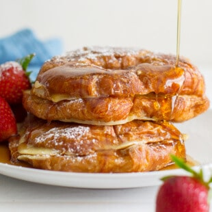 Croissant French Toast with strawberries on a white plate being drizzled with syrup.