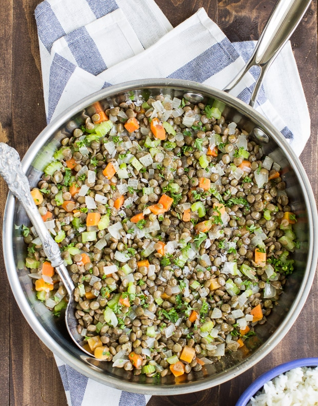 Easy Brown Lentils - a bird's eye view photo of a silver skillet with a cooked mixture of different colorful ingredients with a blue and white cloth - click photo for full written recipe