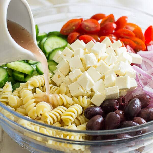 A clear bowl with ingredients prepared to toss for the Greek Pasta Salad, while Homemade Red Wine Vinaigrette is being poured into the bowl from a white serving container.