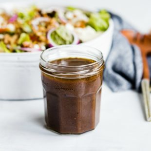 Side shot of balsamic vinaigrette in a glass jar.