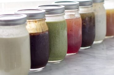 Seven mason jars filled with different salad dressings lined up next to each other.