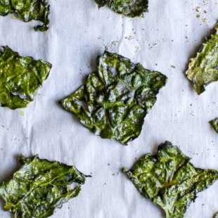 Crispy Kale Chips on parchment paper. y and the tastiest possible way to eat more greens! 2 ingredients and 20 minutes is all you need.