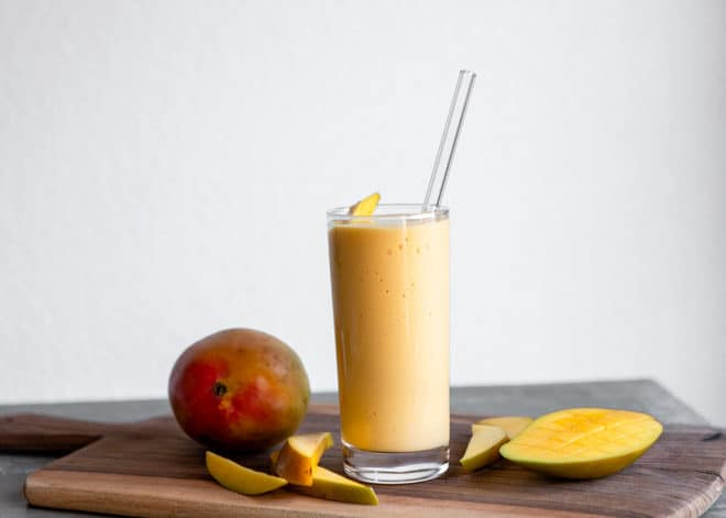 A tropical mango smoothie on a wooden surface.
