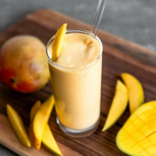 Tropical mango smoothie in a clear glass with a straw and slice of mango as a garnish.