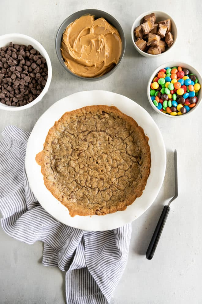 A chocolate chip cookie cake in a white circular dish.
