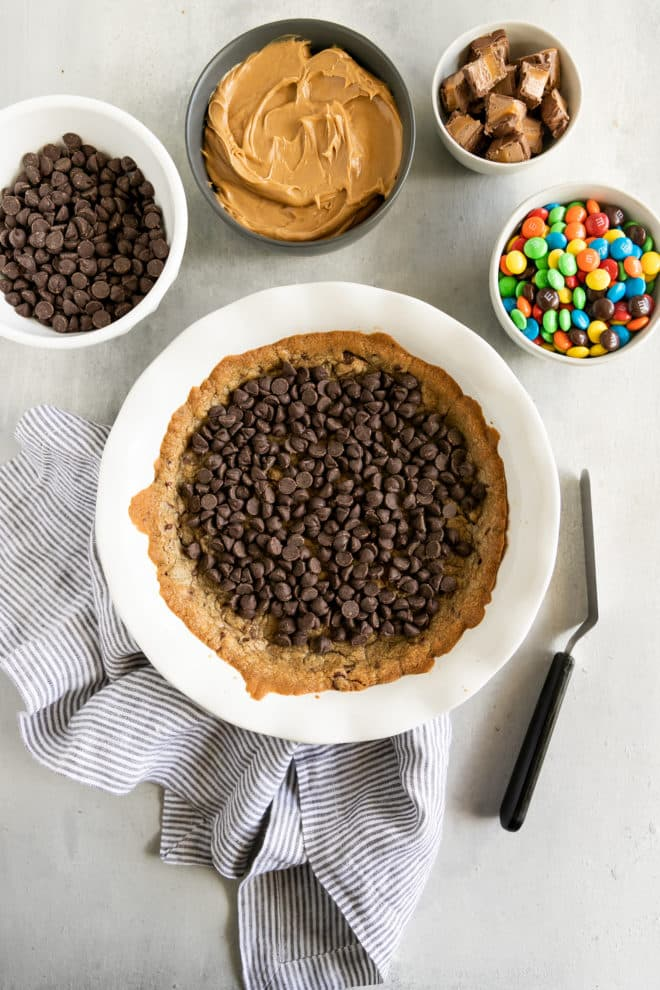 Chocolate chip cookie cake in a white bowl.