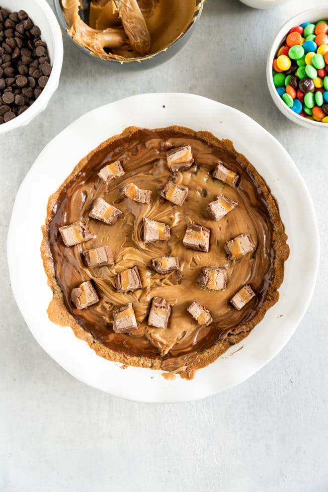 This effortless Chocolate Chip Cookie Cake recipe starts with store-bought cookie dough topped with swirled chocolate chips and peanut butter. Then, decorate it any way you like! Think leftover Halloween candy (as if there is such a thing!) or decorations from your last birthday celebration.