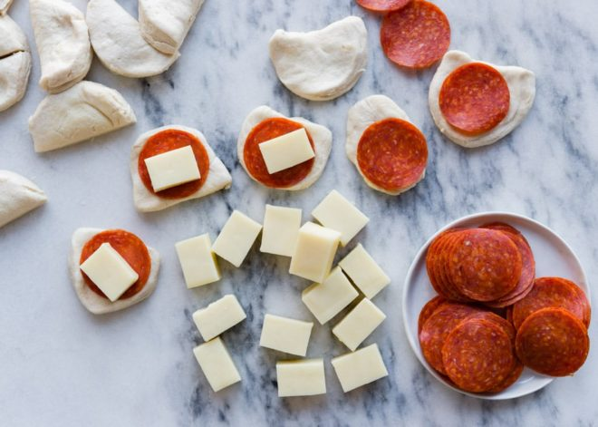 Pepperoni pizza ingredients on a gray countertop.
