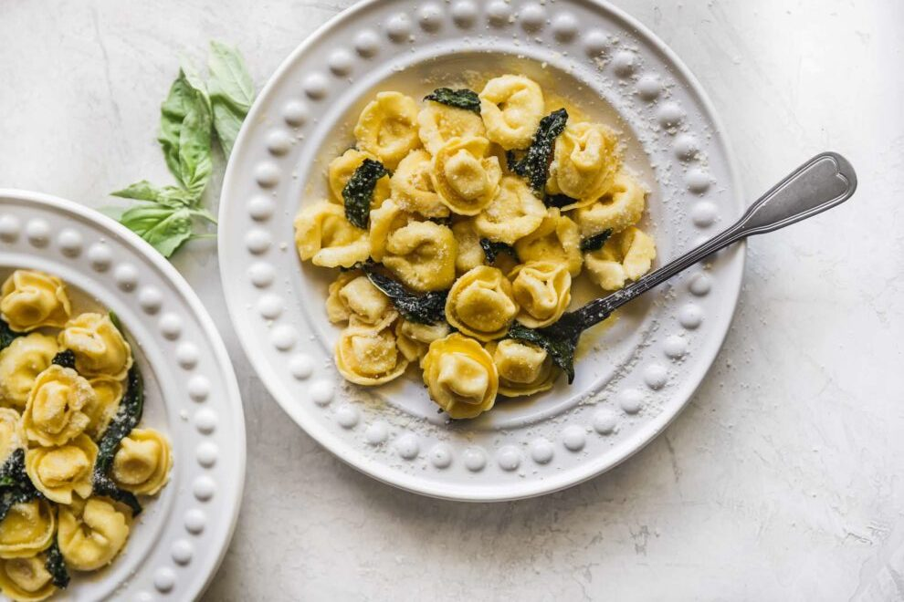 Cheese tortellini on a white round plate.