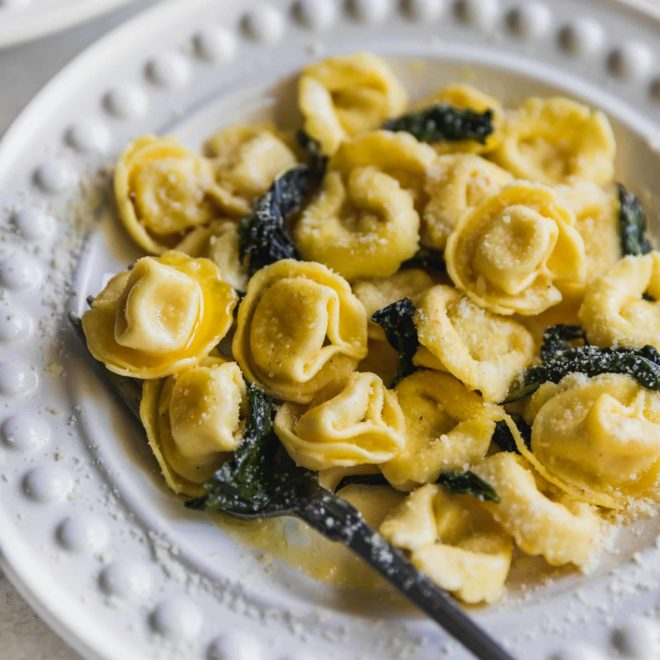 Cheese tortellini on a white plate.