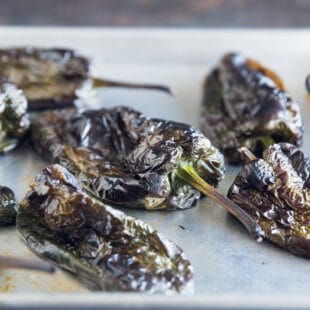 Five freshly roasted poblano chiles on a white background.