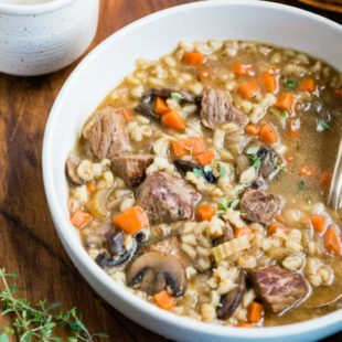 Beef barley soup in a white bowl.