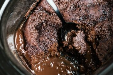 Slow cooker chocolate lava cake in a slow cooker with a silver spoon.