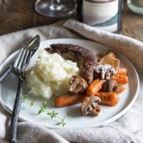 Easy Beef Bourguignon on a white plate with a side of mashed potatoes and vegetables.