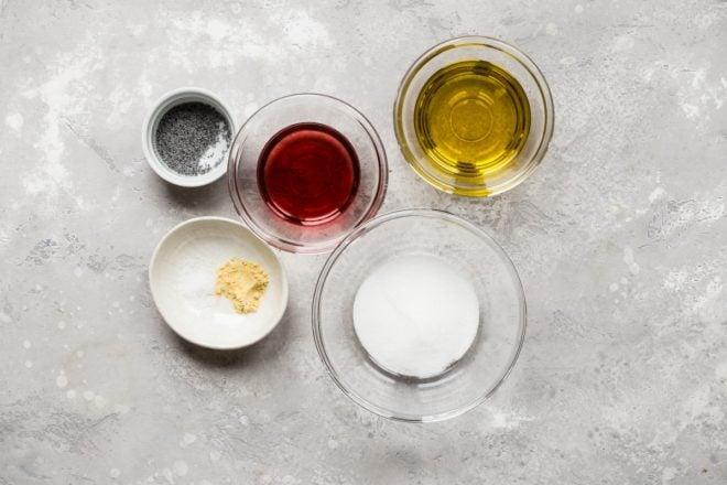 Homemade poppy seed dressing ingredients in various bowls.