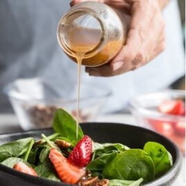 Homemade poppy seed dressing being poured onto a spinach salad.