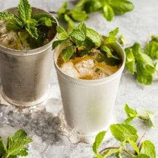 Two mint Juleps in silver glasses surrounded by ice and sprigs of mint.