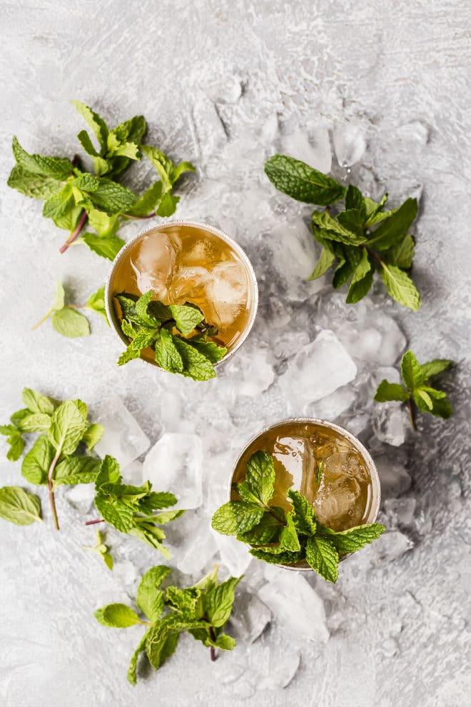 Two mint juleps with mint garnish.