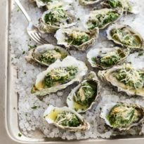 Oysters Rockefeller on a sheet pan with ice.