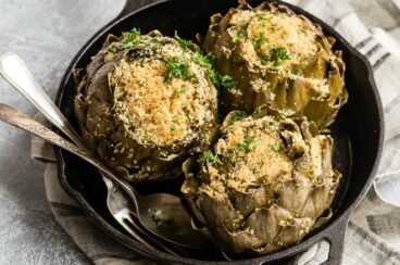 Three stuffed artichokes in a cast iron skillet.