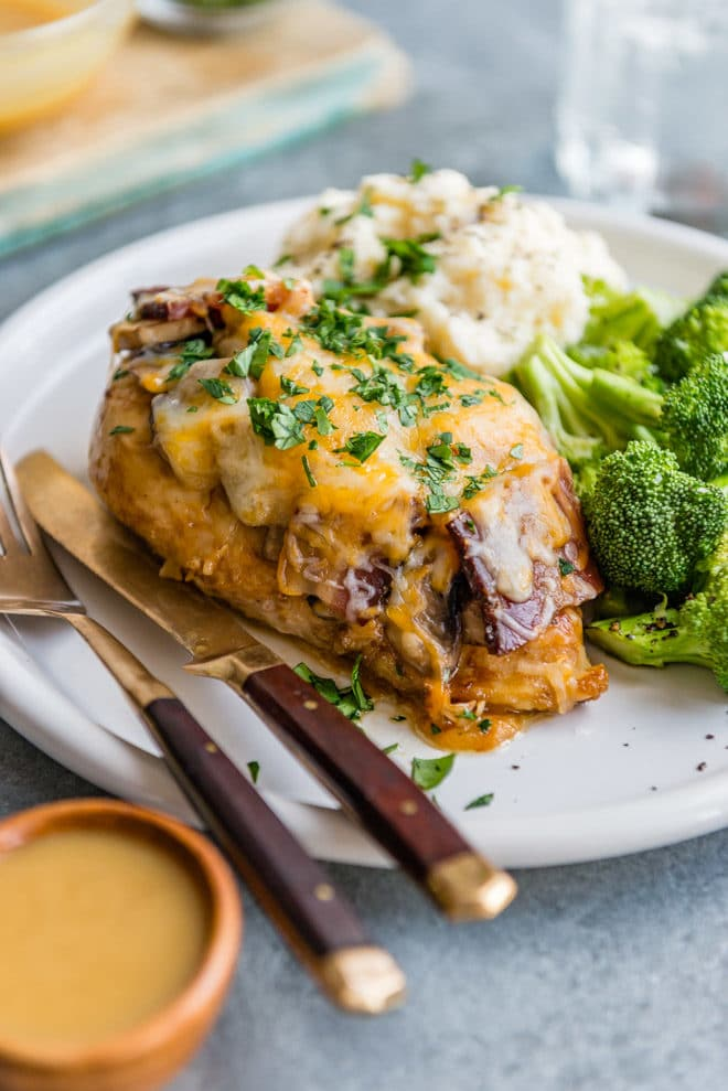 An easy recipe for Alice Springs Chicken, an Outback Steakhouse copycat recipe. Marinade chicken breast in honey mustard sauce, then top with mushrooms, bacon, and way too much cheese! So delicious.