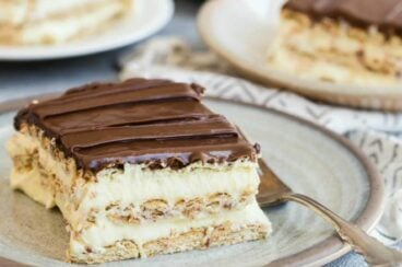 A slice of chocolate eclair cake on a white round plate with a fork.
