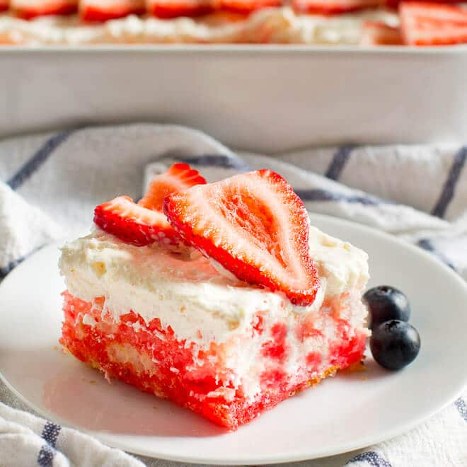 This Strawberry Jello Poke Cake is made with light and airy angel food cake, white chocolate pudding frosting, and plenty of fresh berries!