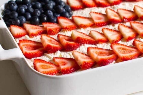 Strawberry Jello Poke Cake in a white dish.