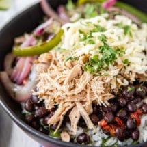 Chipotle carnitas in a black bowl.