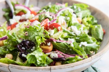 Mediterranean chopped salad in a large wooden serving bowl.